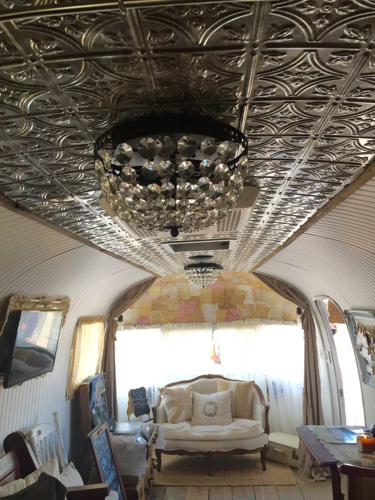After taking the trailer down to the skin and rewiring and repairing leaks the trailer was insulated with spray foam and a 1/4 layer of luan was attached. The white bead board went on over that. The ceiling is a plastic replica of a tin ceiling that is flexible and easy to install. The light fixtures add lots of feminine bling and are from Pottery Barn.