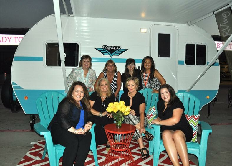 The GoRVing team posing with Jennie Garth in front of the Riverside Retro on display at the Go RVing VIP dinner.