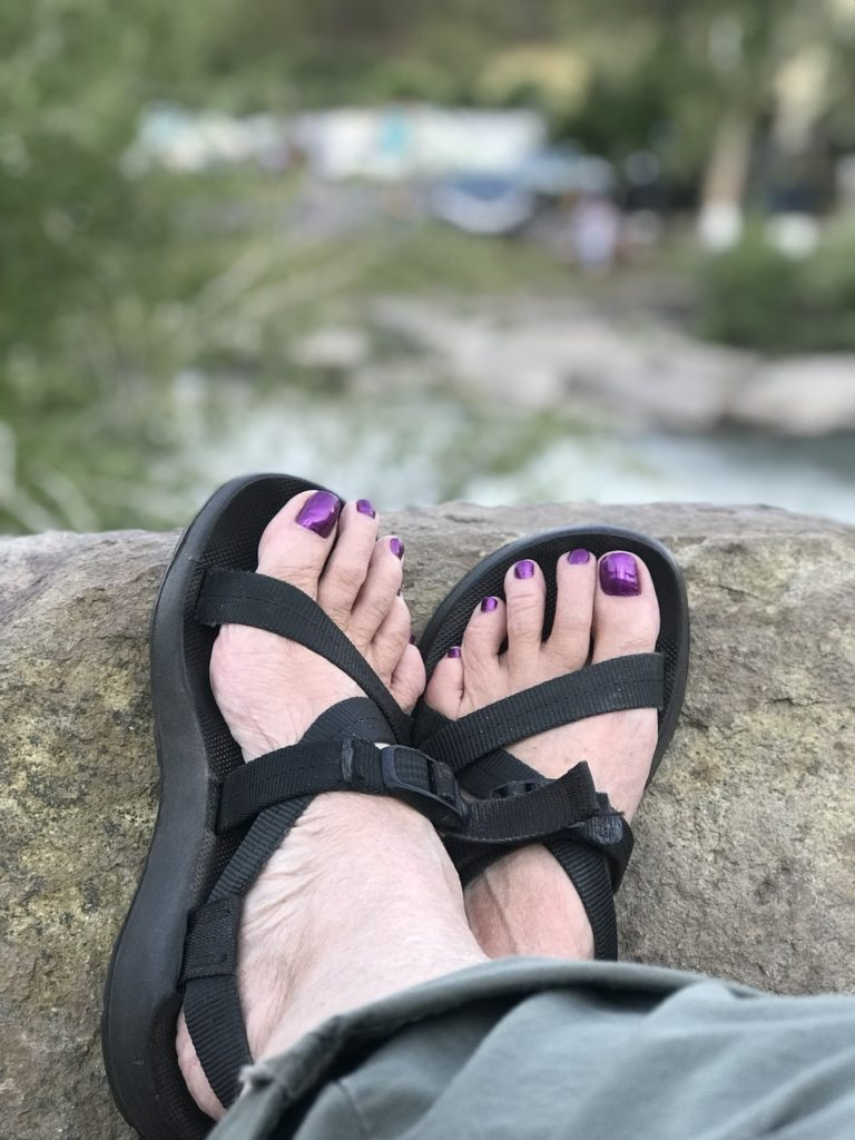 Woman in sandals on riverbank